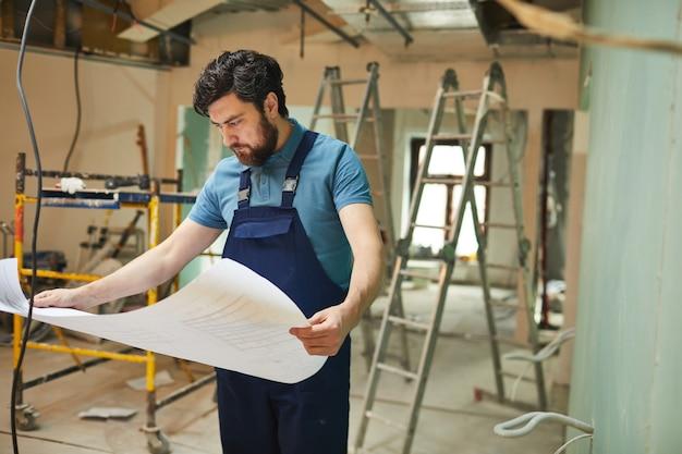 Ritratto di barbuto operaio edile guardando le planimetrie durante la ristrutturazione di casa da solo, copia dello spazio