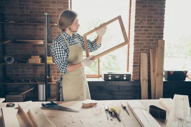 Ritratto di artigiano barbuto in posa nella sua falegnameria