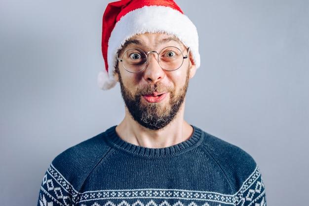 Ritratto di un ragazzo barbuto in santa cappello e occhiali da vista che sembra stupito