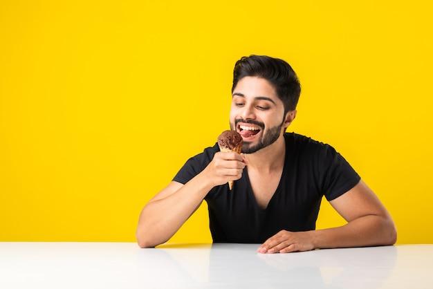 Ritratto di un bel giovane indiano barbuto che mangia il gelato in cono o ghiacciolo mentre è seduto a tavola su sfondo giallo per studio