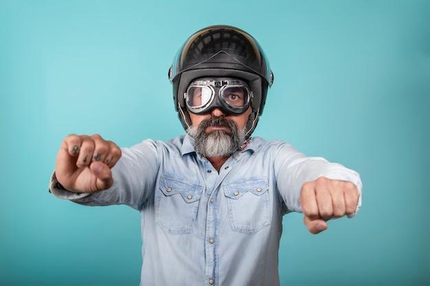 Ritratto di hipster barbuto in camicia di jeans con casco e occhiali che finge di guidare una moto, isolato sulla parete blu dello studio.