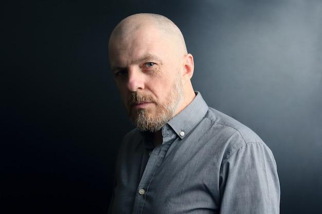 Ritratto di un uomo barbuto su uno sfondo scuro