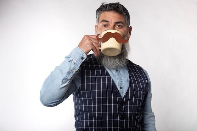 Ritratto di uomo barbuto che beve da una tazza con baffi di carta finta