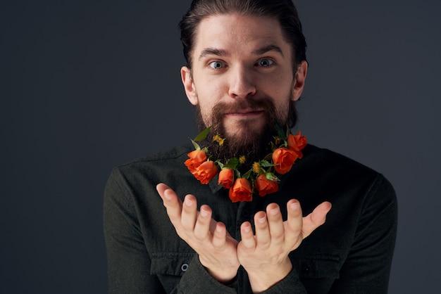 Ritratto di un uomo barbuto fiori romanticismo decorazione regalo sfondo scuro. foto di alta qualità
