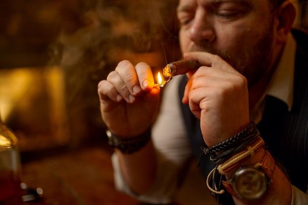 Ritratto di uomo barbuto accende un sigaro con un fiammifero, vista del primo piano. cultura del fumo di tabacco, sapore specifico. svaghi fumatore maschio in ufficio