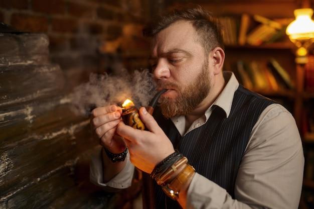 Il ritratto dell'uomo barbuto accende la pipa fumante con un fiammifero, vista del primo piano