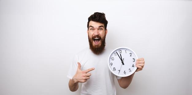 Ritratto di uomo barbuto che punta all'orologio, guarda