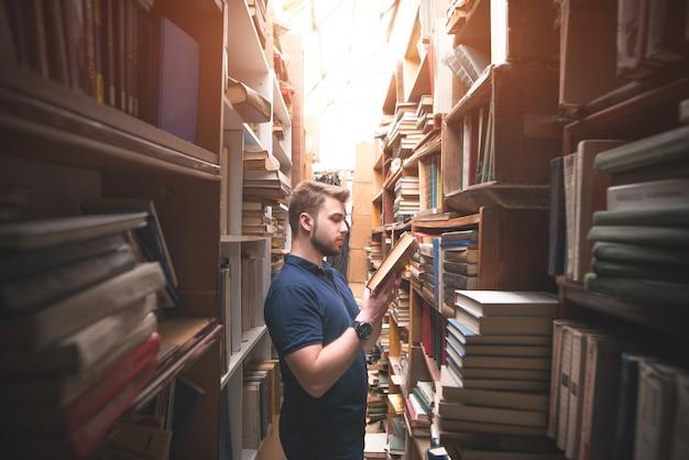Ritratto di un uomo barbuto che legge un libro in una vecchia biblioteca pubblica