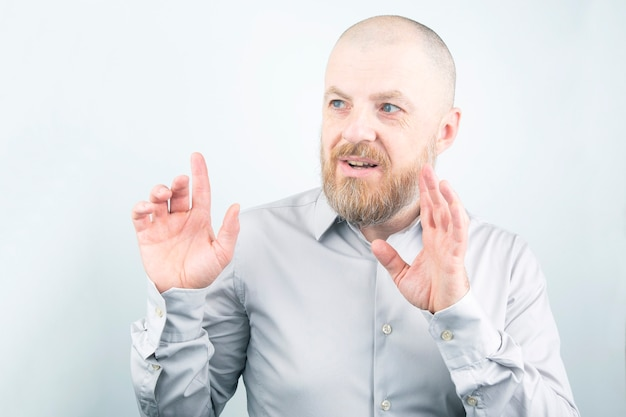 Ritratto di un uomo barbuto in una camicia con le braccia alzate