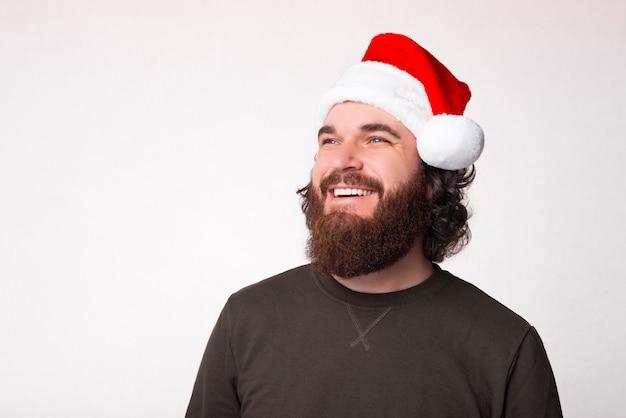 Ritratto di uomo barbuto che indossa il cappello di babbo natale sorridendo e guardando lontano