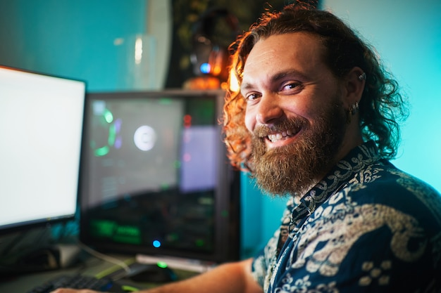 Ritratto di uomo barbuto con computer che guarda e sorride alla telecamera