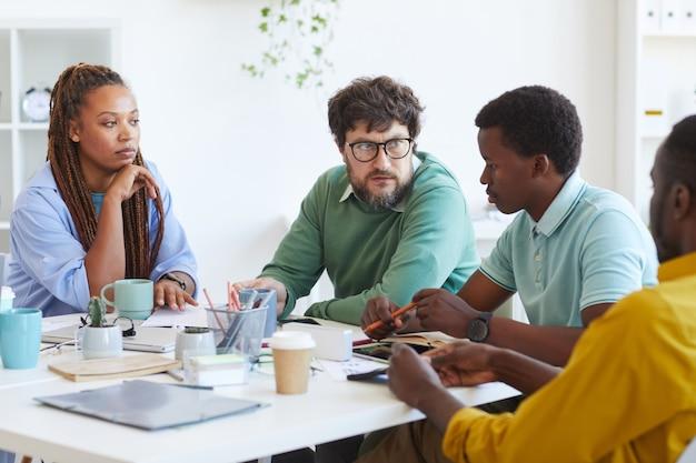 Ritratto di barbuto manager maturo parlando al team multietnico di affari mentre discute i piani durante la riunione in ufficio