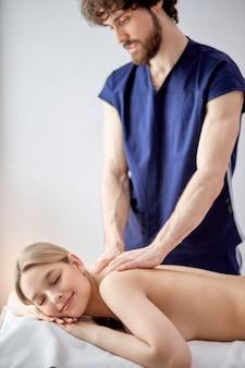 Ritratto del massaggiatore barbuto piacevole in uniforme che fa con attenzione massaggio sulla parte posteriore della femmina, donna caucasica bionda che si trova sulla pancia che si rilassa, godendo. copia spazio per la pubblicità. focus sulla donna