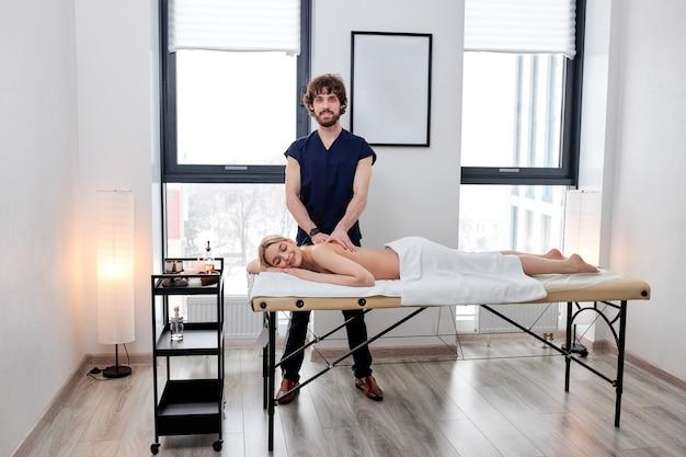 Ritratto di un bel massaggiatore barbuto in uniforme che fa con cura massaggio sulla schiena femminile bionda caucasica ...