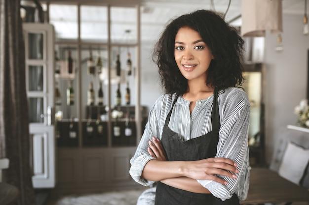 Ritratto di una bella ragazza afroamericana che indossa camicia e grembiule in ristorante