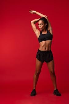 Ritratto di bella donna afroamericana in abiti sportivi neri che allunga il suo corpo, isolato sopra la parete rossa