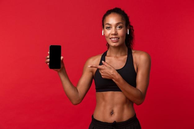 Ritratto di bella donna afroamericana in abiti sportivi neri utilizzando smartphone e auricolari, isolati sopra la parete rossa
