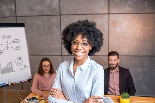 Ritratto di una bella donna d'affari africana con i colleghi sullo sfondo in ufficio