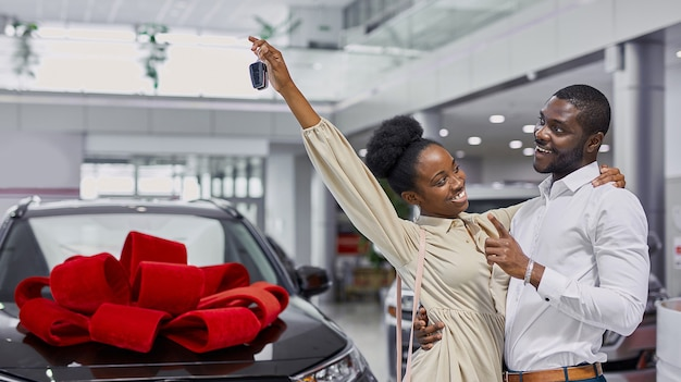Ritratto di bella coppia sposata africana è venuto in concessionaria per acquistare la loro prima auto di famiglia