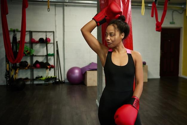 Ritratto di bella donna sportiva africana, attraente pugile femminile in abbigliamento sportivo nero e guantoni da boxe rossi, guardando di lato, appoggiato a un sacco da boxe in palestra di boxe. concetto di stili di vita attivi