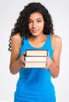 Ritratto di una bella donna afroamericana che tiene i libri isolati su una parete bianca