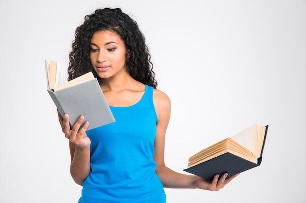 Ritratto di una bella donna afroamericana che tiene due libri isolati su una parete bianca