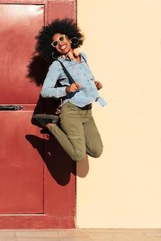 Ritratto di bella donna afroamericana che salta in strada.