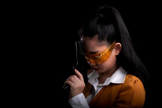 Ritratto bella donna asea che indossa un abito giallo con una mano che tiene la pistola alla superficie nera, capelli lunghi giovane ragazza sexy con una pistola guarda la telecamera, belle donne si erge con una pistola