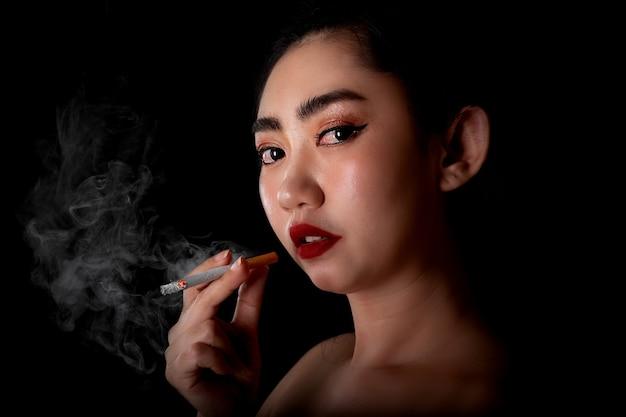 Ritratto bella giovane donna asiatica con un tabacco da pipa fumante sullo sfondo nero