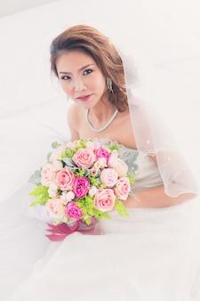 Ritratto di bella sposa asiatica seduta nel camerino e con in mano un mazzo di fiori con sfondo bianco persiane.