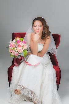 Ritratto di una bella sposa asiatica seduta su una sedia rossa che tiene in mano un mazzo di fiori e mette la mano sotto il mento su sfondo grigio.