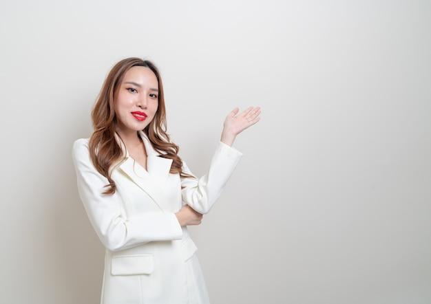 Ritratto bella donna d'affari asiatica con la mano che presenta o punta su sfondo bianco