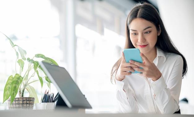 Ritratto di bella donna d'affari asiatica che utilizza smartphone inviando un messaggio online mentre è seduto alla scrivania dell'ufficio in un ufficio moderno.