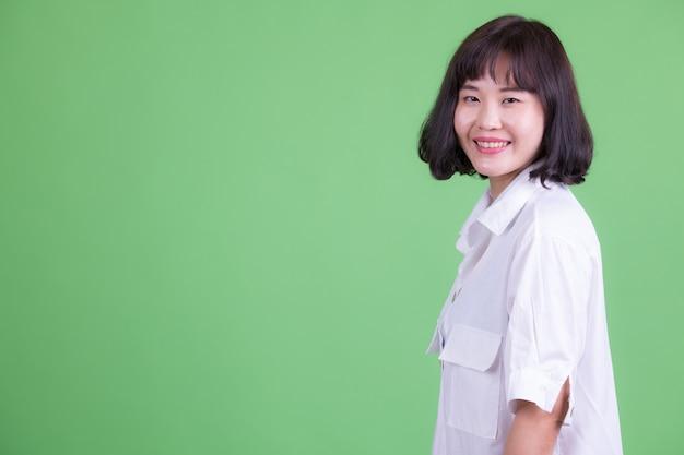 Ritratto di bella donna d'affari asiatica con i capelli corti contro la chiave di crominanza o la parete verde