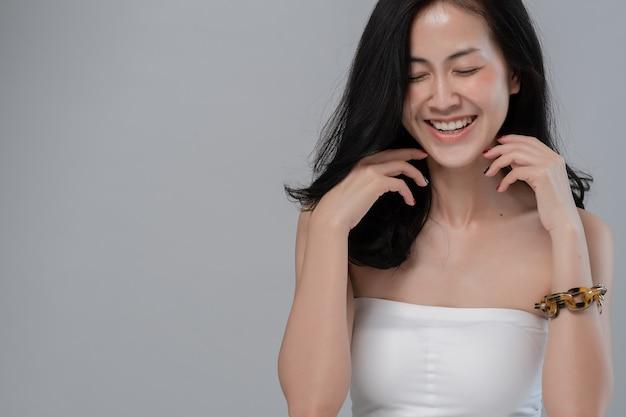 Ritratto di una bella ragazza asiatica con un trucco da sera, modello sorridente sul grigio