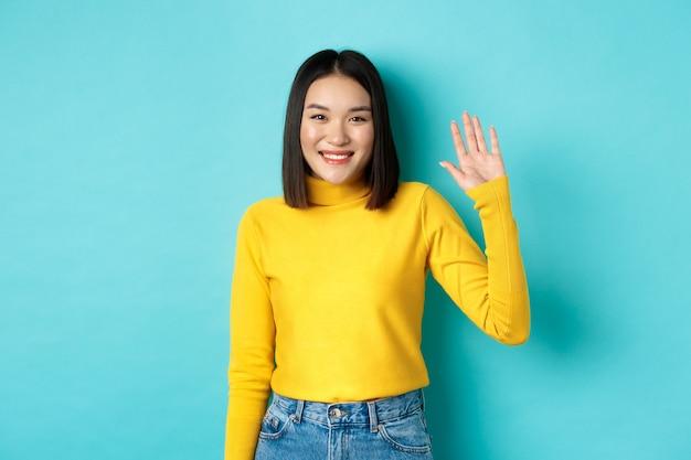 Ritratto di bella ragazza asiatica con un sorriso felice, agitando la mano per dire ciao, salutandoti con un viso amichevole, in piedi su sfondo blu