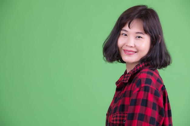 Ritratto di bella donna asiatica hipster con i capelli corti contro la chiave di crominanza o la parete verde