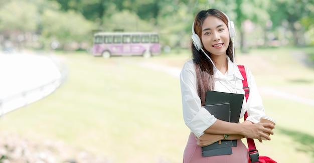 Ritratto di bello studente universitario asiatico con la cuffia e la borsa a tracolla rossa che tiene libro e tazza di caffè mentre stando all'aperto.