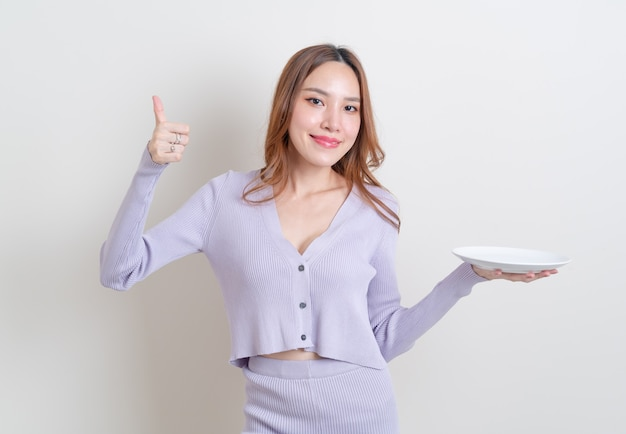 Ritratto bella donna asiatica che tiene piatto vuoto su sfondo bianco