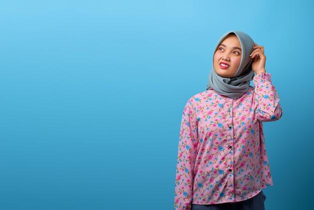 Il ritratto di una bella donna asiatica che sembra preoccupata ha problemi a pensare su sfondo blu