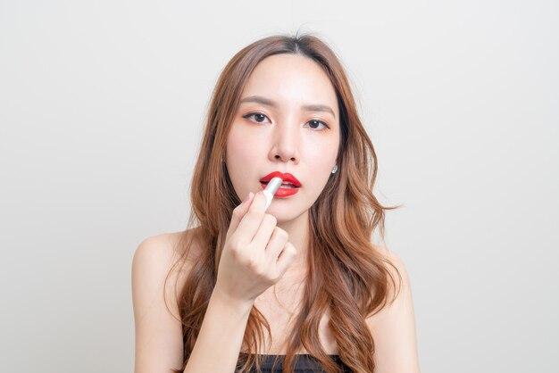 Ritratto bella donna asiatica che si trucca e usa il rossetto rosso su sfondo bianco