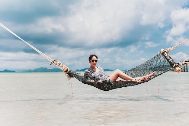 Bella donna asiatica del ritratto che si siede sull'amaca nel mare in vacanza.