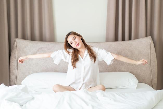 Ritratto bella donna asiatica sveglia sul letto la mattina