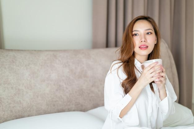 Ritratto, bella donna asiatica, sveglia, e, presa a terra, tazza caffè, o, tazza, letto, in, morning
