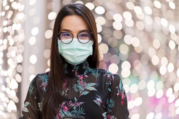 Ritratto bella donna asiatica indossare la maschera per il viso con sfondo sfocato bokeh