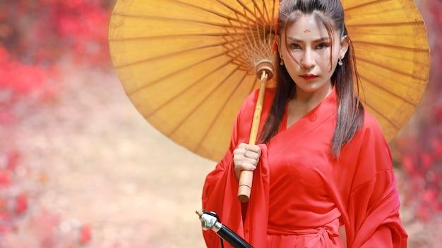 Ritratto di bella donna asiatica che indossa un costume cinese da guerriero rosso \