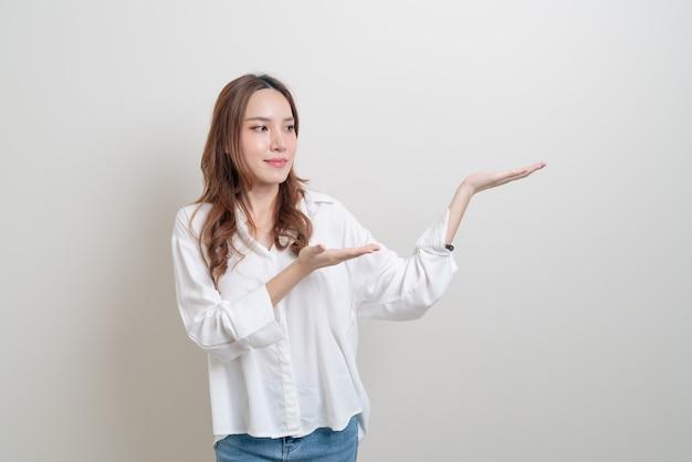 Ritratto bella donna asiatica con la mano che presenta o indica su sfondo bianco