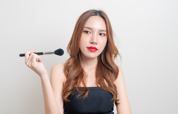 Ritratto bella donna asiatica con pennello trucco su sfondo bianco