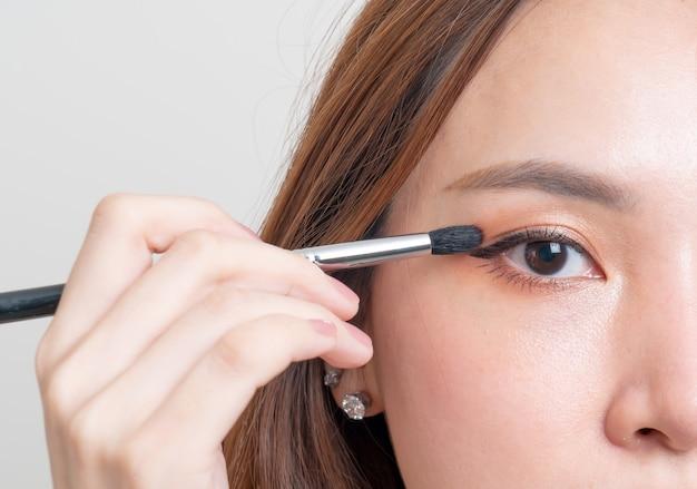 Ritratto bella donna asiatica con pennello per gli occhi trucco su sfondo bianco