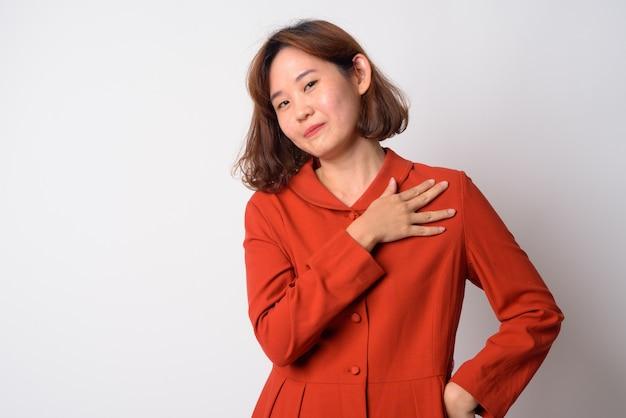 Ritratto di bella donna asiatica con i capelli corti contro il muro bianco